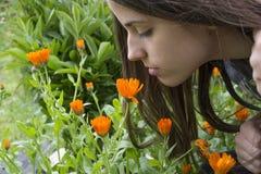Girl smells flowers. Girl smells orange flowers in the garden Stock Images