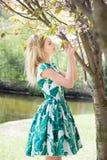 Girl smells sakura in park. Springtime, spring. Girl smells sakura. Springtime, spring Stock Photo