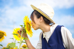 Girl smells sunflower in nature. Thailand Royalty Free Stock Images
