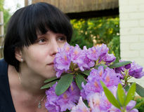 The girl smells violet flowers. Alone Stock Photography