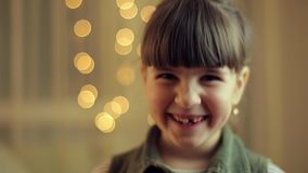 Girl smile into camera. Six year old girl smile into camera with lights bokeh in the background