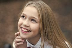Girl smile with cute face, beauty. Little child smiling with long blond hair, hairstyle outdoor. Baby beauty, hair and