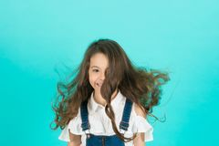 Girl smile with flowing long wavy hair on blue background. Child smiling with healthy brunette hair. Kid beauty salon concept. Haircare, hairstyle, hairdresser Royalty Free Stock Images