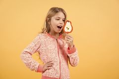 Girl smile with lollipop on orange background royalty free stock photography