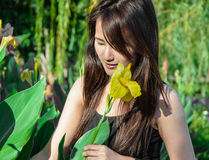 Girl smile and look into flower Stock Photos