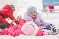 The girl with a smile looking at another girl rolled down the hills. Two girls in the winter ride on a snowy hill surrounded by other children Stock Photo