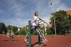 Girl with a smile. Practice. Gym in the open-air park. Exercise for the legs. Outdoor gym stock images