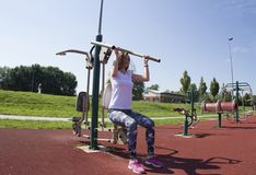 Girl with a smile. Practice. Gym in the open-air park. Hands and back exercises.Outdoor gym stock photos