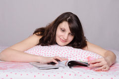 Girl with smile reading a magazine article Stock Photos