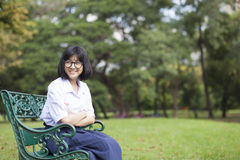 Girl smile and sitting on the bench. Stock Image