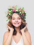 The girl with a smile in a wreath of pink and white roses. Corrects hairstyle Royalty Free Stock Photography