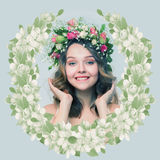 The girl with a smile in a wreath of pink and white roses in the. Form of spring emblem on a gray-blue background Stock Photo