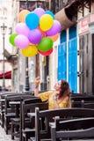 A girl smiles with ballons in hand stock photos
