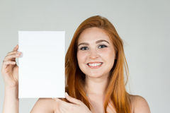 Girl smiles and holds blank paper for publicity. The teenager is. Beautiful girl is presenting a blank paper for advertising content. She is smiling and looks at royalty free stock photo