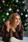 Girl smiles near Christmas tree Stock Photo