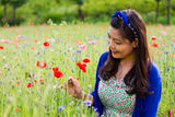 Girl smiles in poppy field Stock Photos