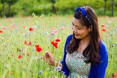 Girl smiles in poppy field Stock Photos