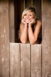 Girl smiles from shed. Young beautiful woman smiles from shed Royalty Free Stock Images