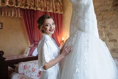 The girl smiles and shows her girlfriend her chic wedding dress. Make-up and hairstyle the bride has already done. She. Smiles and looks forward to the stock image