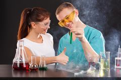 The girl smiles and shows a thumbs-up gesture while the guy is holding a flask with a green liquid. Happy young chemistry couple, the girl smiles and shows a Stock Photo
