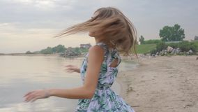 The girl smiles against the sea. The girl smiles and spin round against the sea stock footage