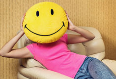 Girl and smiley cushion. Royalty Free Stock Images