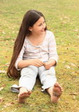 Girl with smileys on toes and sign STOP on soles. Barefoot kid - funny girl with fairly long brown hair and with ten smileys - small faces on toes and signs STOP Stock Photography