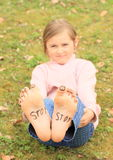 Girl with smileys on toes and sign STOP on soles. Barefoot kid - funny girl with ten smileys - small faces on toes and signs STOP on soles of her bare feet Royalty Free Stock Image