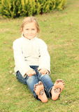 Girl with smileys on toes and soles. Barefoot kid - funny girl with ten smileys - small faces on toes and two on soles of her bare feet Stock Photography