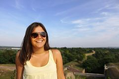 Girl smiling. Beautiful cute female having fun outdoor with sunglasses Royalty Free Stock Photography