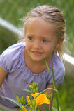 Girl Smiling. A four year-old girl smiles while peering back at her family on beautiful summer day Royalty Free Stock Image