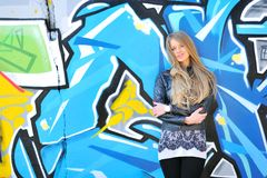 Girl smiling against grafitti wall. Blonde girl smiling against grafitti wall stock images
