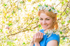 Girl smiling on the background of blossoming cherry Stock Images
