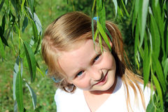 Girl smiling besides the leaves of willow Royalty Free Stock Image