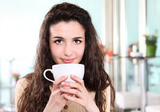Girl smiling in cafe, drink coffee  with cup in hand Stock Images