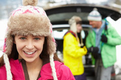 Girl Smiling At Camera Whilst Family Load Skis Stock Image