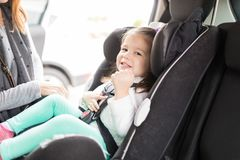 Girl Smiling On Car Seat. Portrait of smiling girl sitting in car showing excitement for road trip royalty free stock photos
