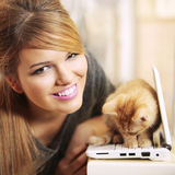 Girl smiling and cat kitten on laptop Royalty Free Stock Image