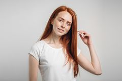 Girl smiling with closed eyes touching her red hair over white background Royalty Free Stock Image