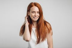 Girl smiling with closed eyes touching her red hair over white background. Happy beautiful girl smiling with closed eyes touching her red curly hair over white Royalty Free Stock Photography