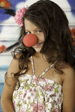 Girl smiling with clown nose. Girl making funny face with smile and dimples with clown nose Royalty Free Stock Photos