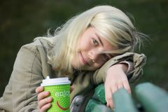Girl smiling. With a coffee Cup with the inscription `Enjoy Royalty Free Stock Photography