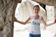The girl is smiling in doorway of the old caves. Stock Image
