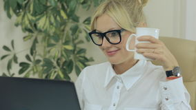 Girl smiling, drinking coffee and looking at stock footage