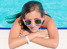 Girl smiling at the edge of a swimming pool. Beautiful hispanic teenage girl with colorful sunglasses smiling at the edge of a swimming pool Stock Photography