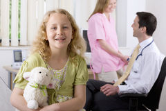 Girl smiling in examination room with doctor and nurse in background Stock Photos