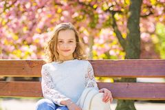 Girl on smiling face sits on bench, sakura tree on background, defocused. Spring walks concept. Cute child with backpack stock images