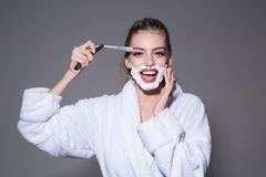 Girl on smiling face wears bathrobe, grey background. Lady play with sharp blade of straight razor. Barber and shaving stock image
