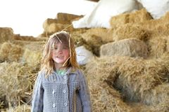 Girl smiling on a farm with hay in hair Stock Images