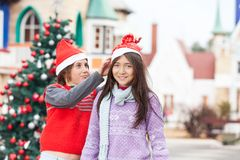 Girl Smiling While Friend Putting Santa Hat On Her Stock Image